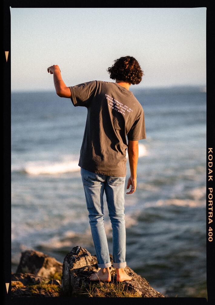 Man standing on rock in blue denim jeans for Surf Dive n Ski Days in Denim