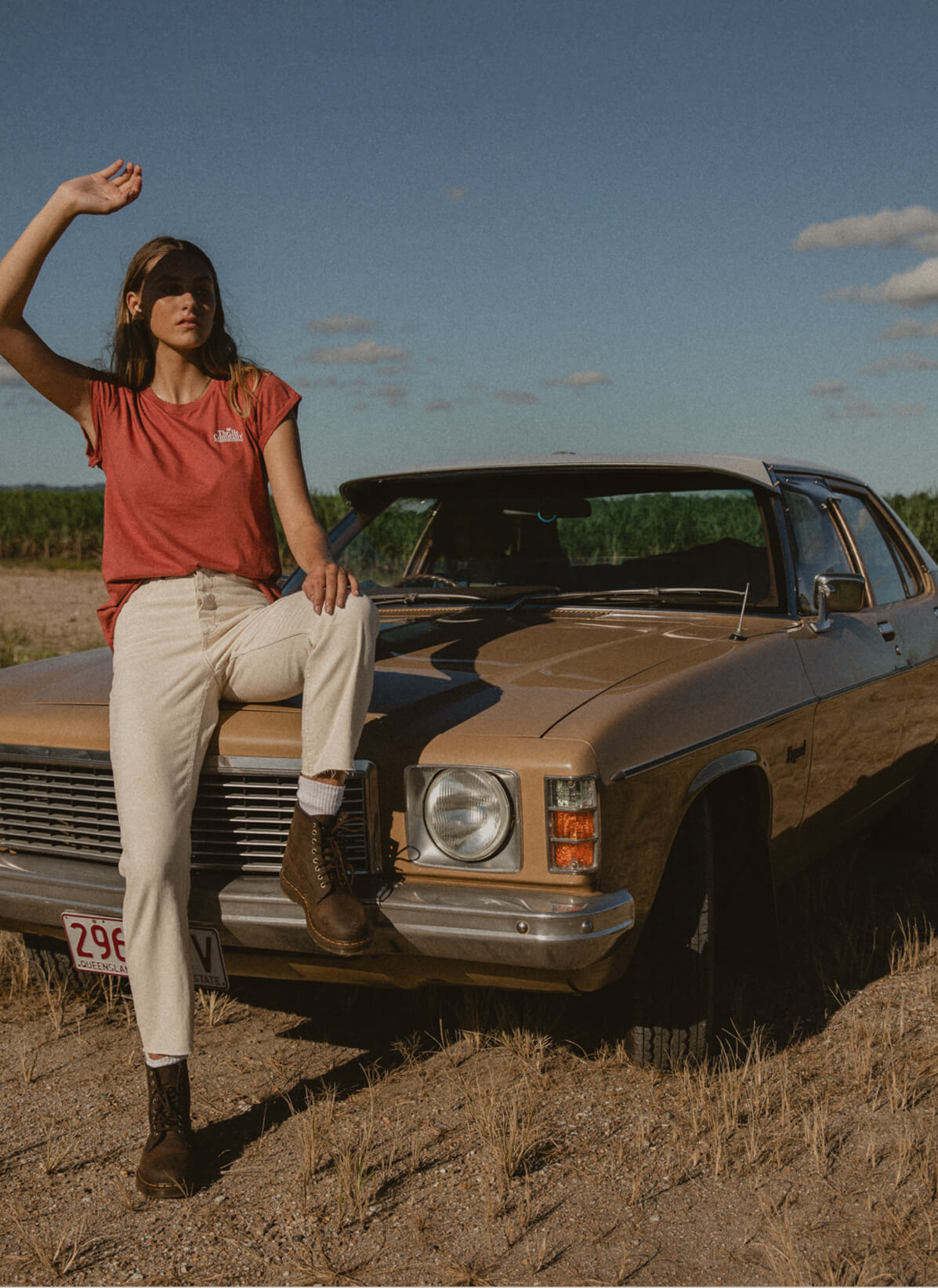 Girl leaning on car in white denim straight jeans