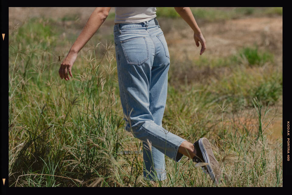 Back of thrills blue denim jeans with women spinning her arms