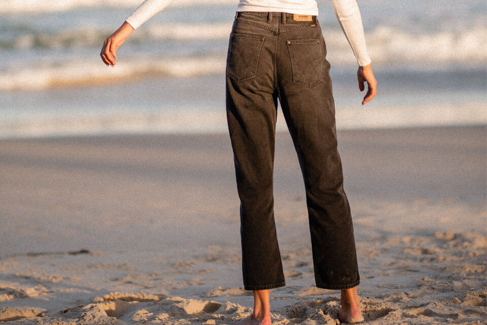 Back of women wearing black wrangler jeans with arms twirling